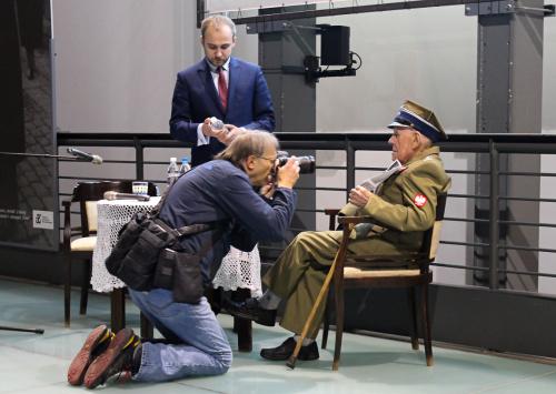 Bohater pozuje do zdjęć przed spotkaniem poświęconym jego osobie